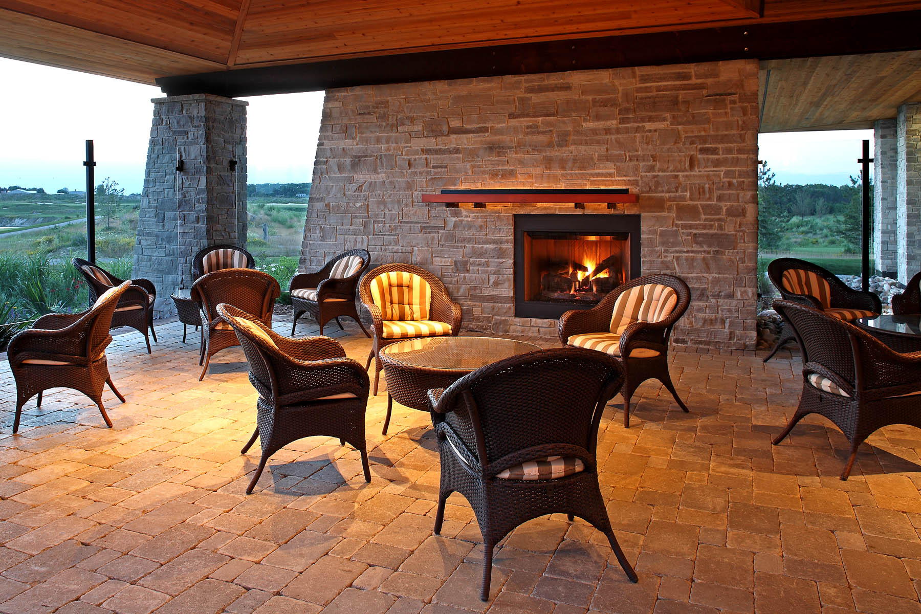 Covered outdoor patio with wicker chairs and tables, stone floor and wall fireplace feature and wood tiered ceiling looking out to green field
