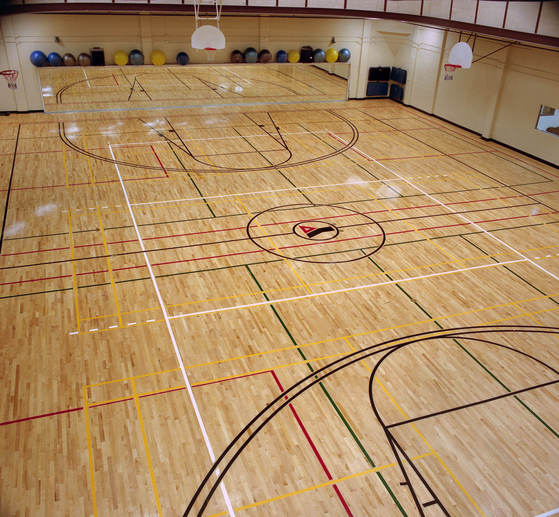 Gymnasium with wood floor with the Y logo, basketball nets and mirrored wall with yoga balls