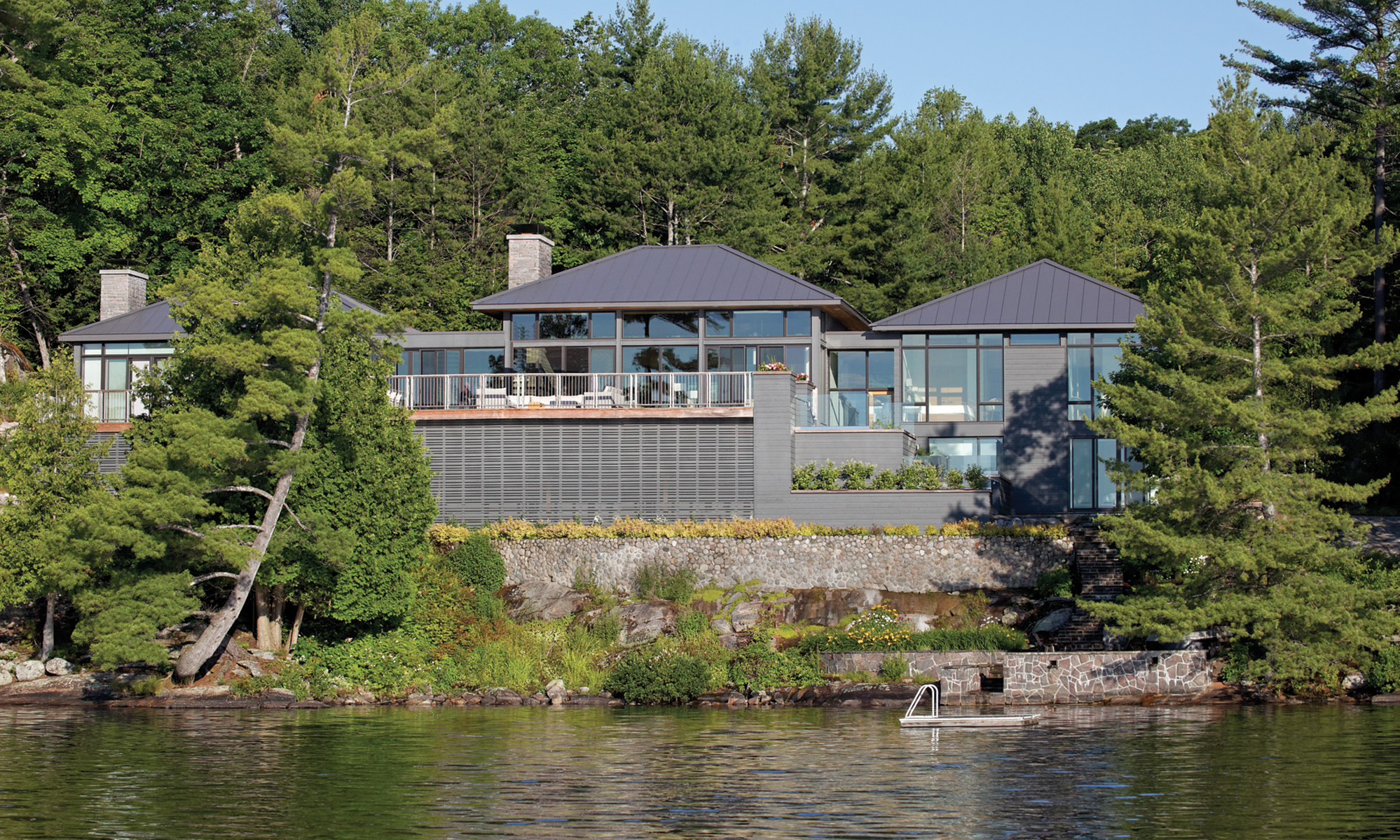 View of elevated cottage from lake featuring glass windows and large upper outdoor patio nestled in thick tree line