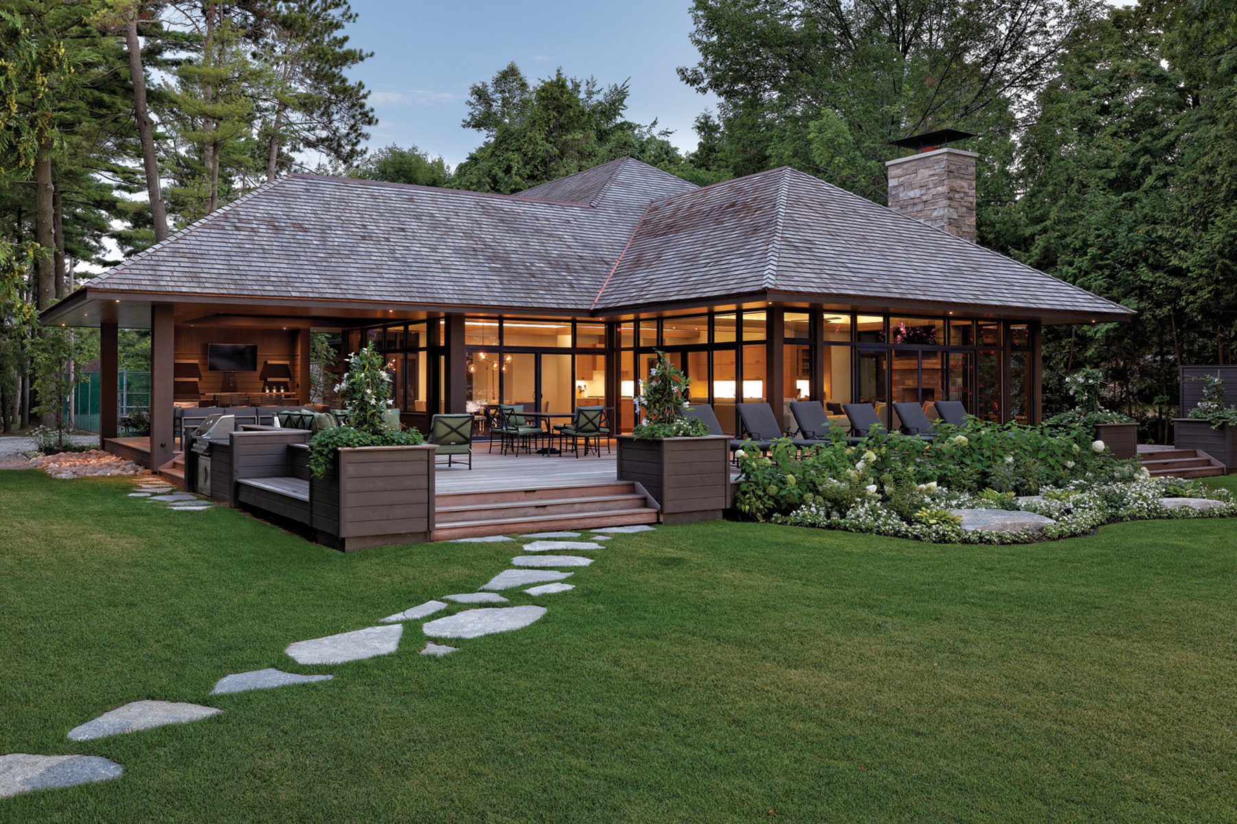 Illuminated cottage with stone walkway across front lawn to large deck at entrance with lounge chairs and gardening in front