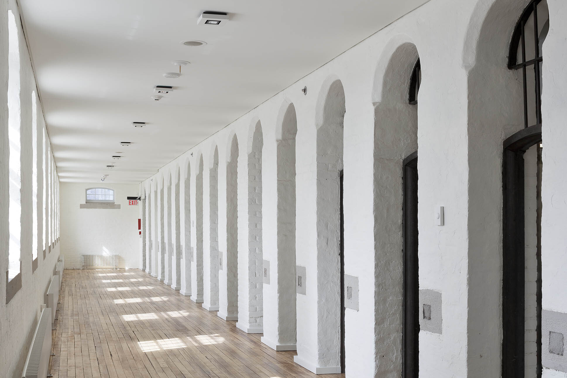 Original cells with archways on right in white corridor with wood floors and windows on left