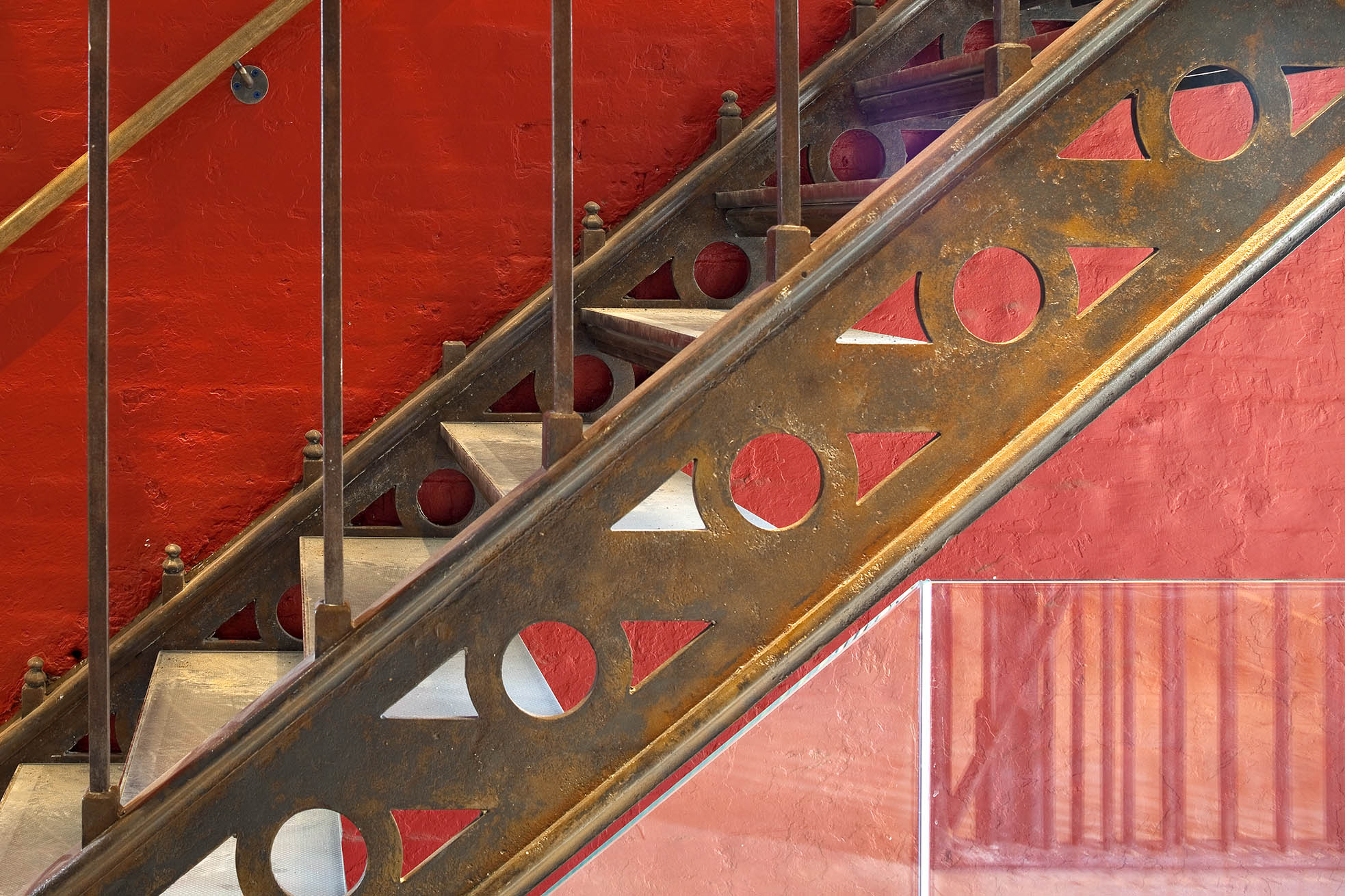 Detail of copper staircase with red painted brick wall in background