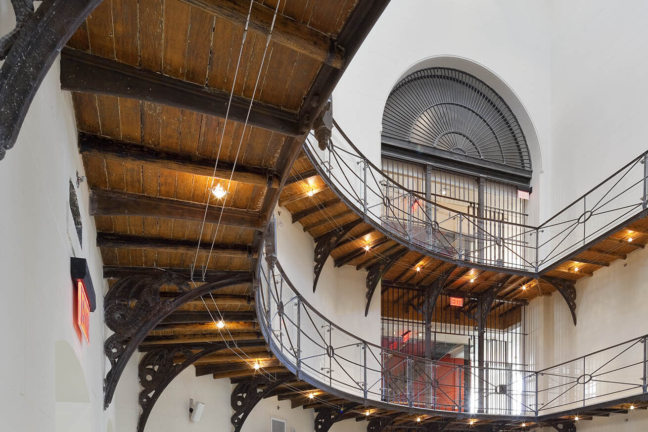 Triple height atrium space with steel railings. under lit wood perimeter corridors and large archway with steel framed window
