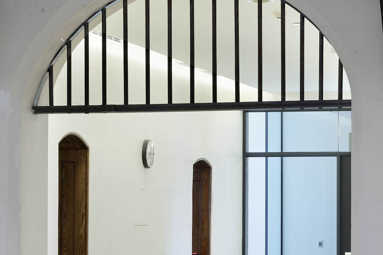 White corridor with wood door archways, bar detailing and window wall