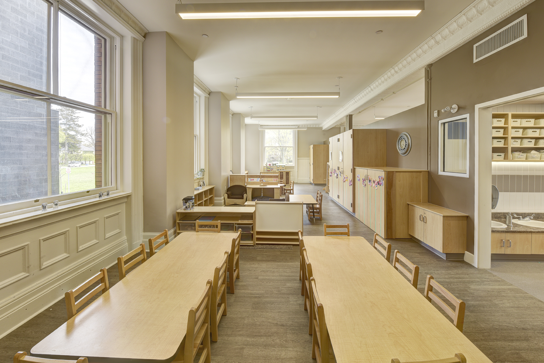 Children's classroom with long wooden tables and chairs, bookshelves, storage cupboards and large bright windows