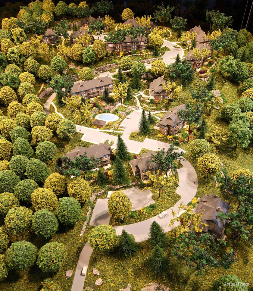 Aerial view of site showing clusters of buildings in lush forest with pool