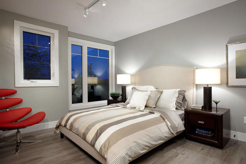Bedroom with large windows, track lighting, grey walls and red chair