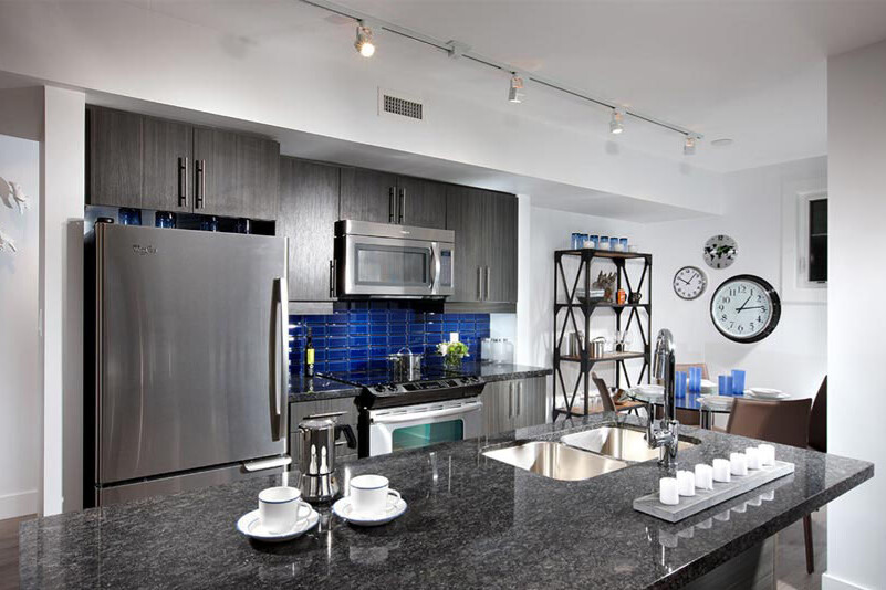 Kitchen with large island, stainless steel appliances, blue back splash, white walls and track lighting