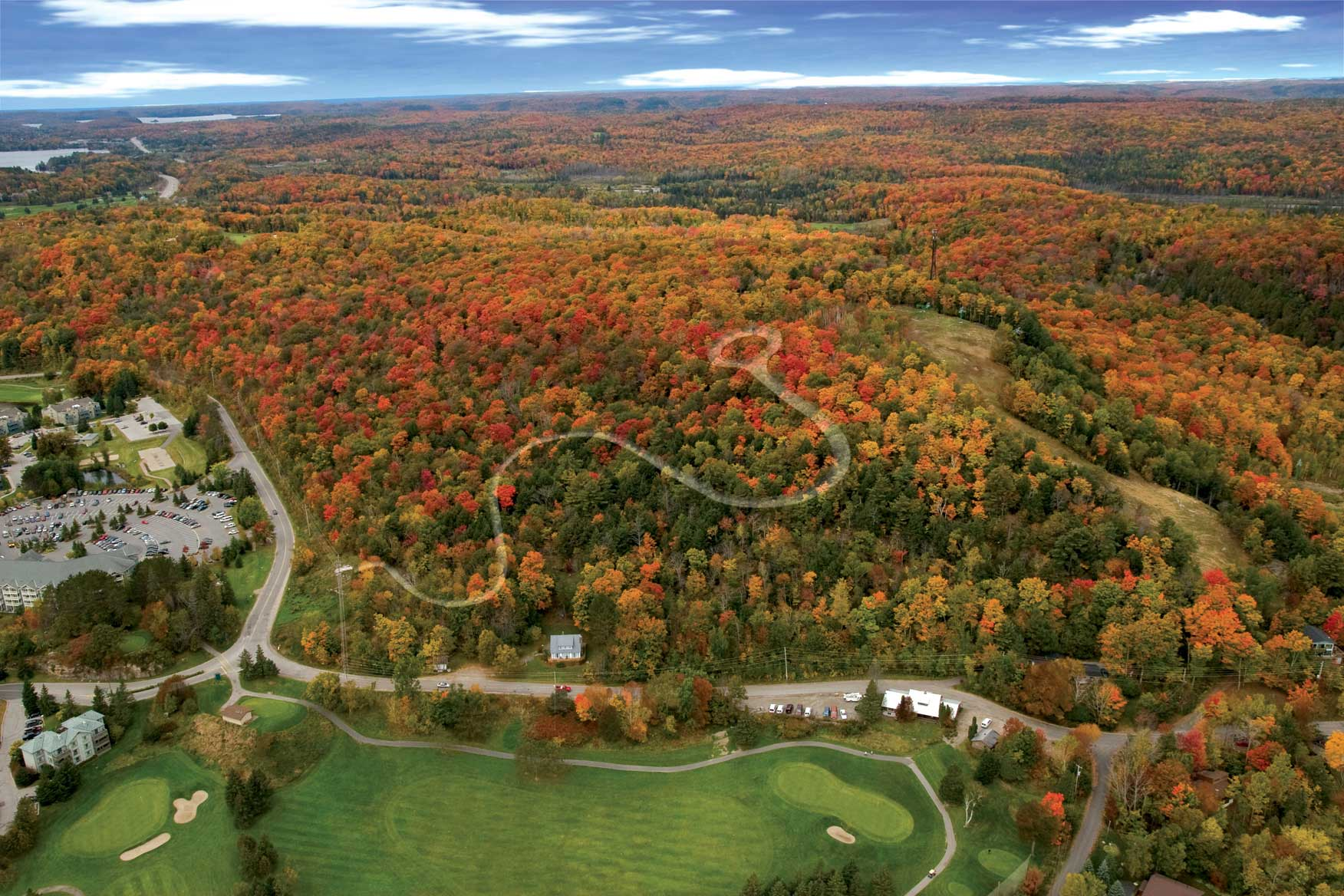 Aerial view of region showing winding driveway into site with autumn leaves