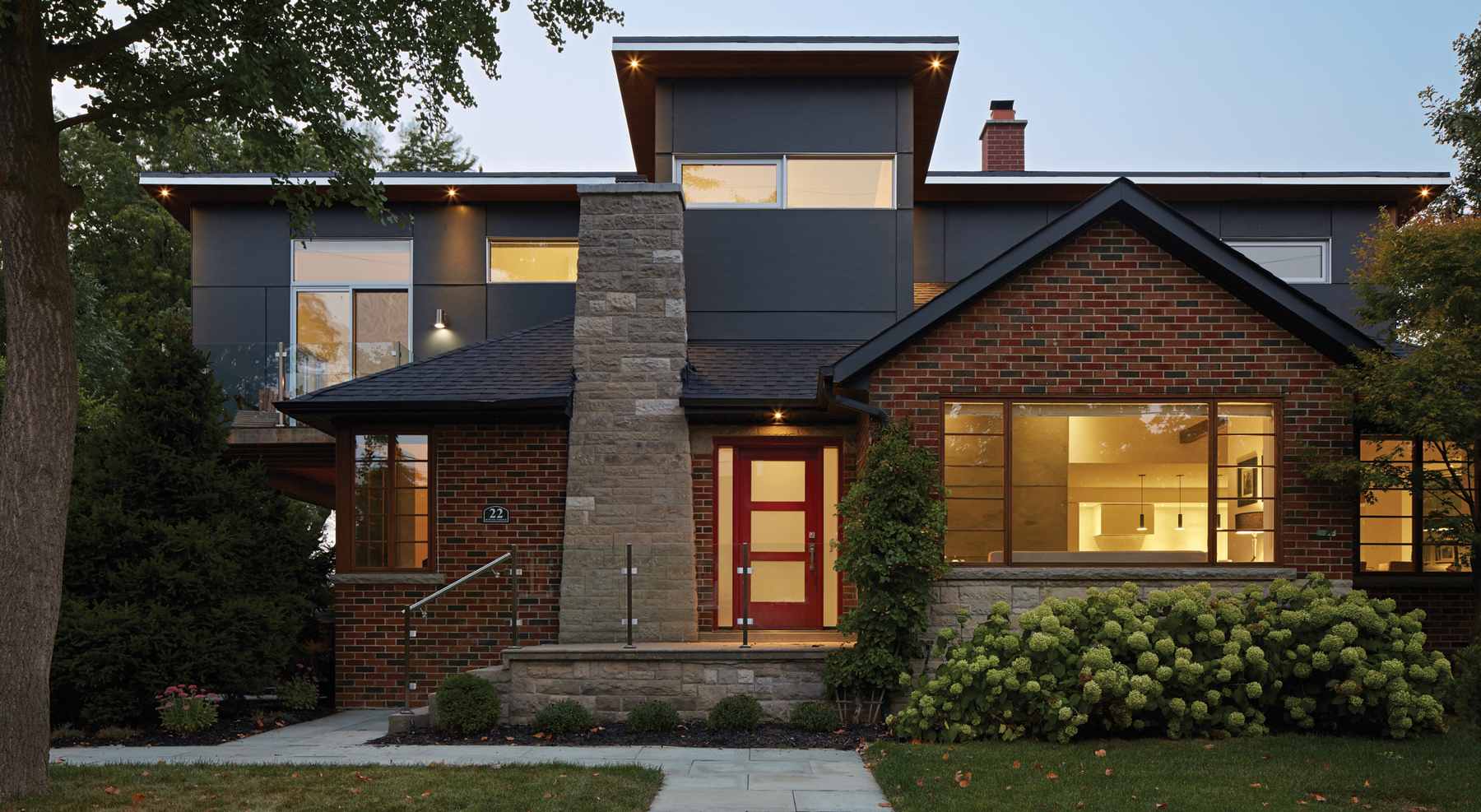 Illuminated original red brick house with second storey addition in the back and landscaped front yard at dusk