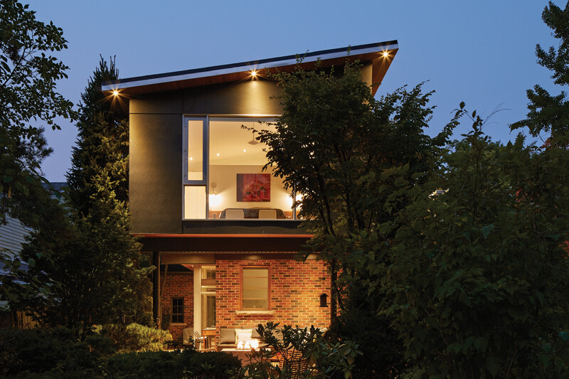 Exterior view of illuminated back facade from tree filled backyard highlighting large second storey bedroom window at dusk