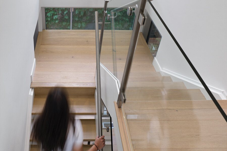 Woman on open wooden staircase with glass partition railing and double height feature window