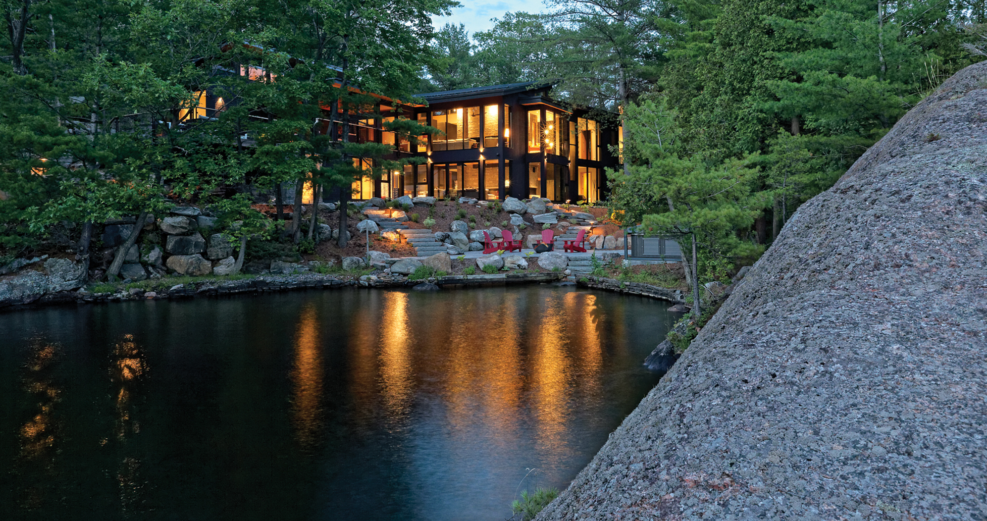 View from lake of red Muskoka chairs with stone staircase leading up to illuminated glazed cottage nestled in trees and rocks at dusk