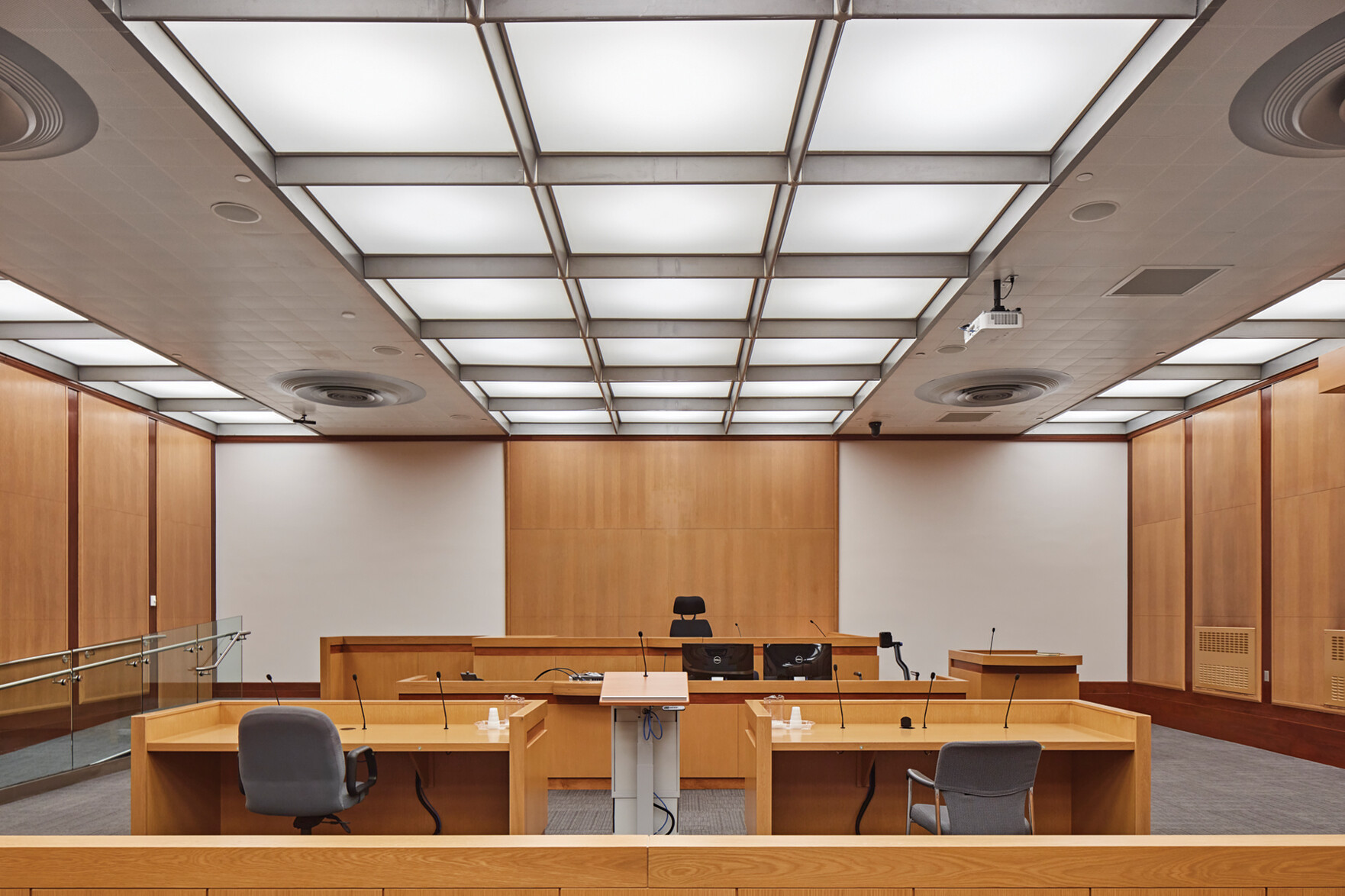 Courtroom with millwork benches for prosecution, defense, judge and witness, with wood paneling on walls and grid panel lighting