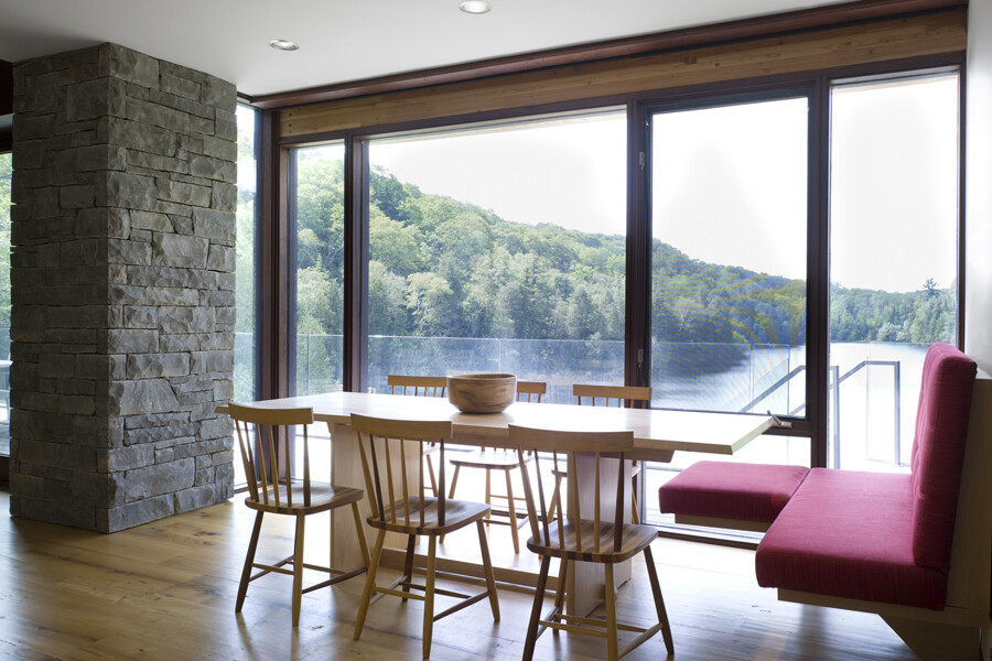 Dining room looking through floor to ceiling glass wall to lake and trees