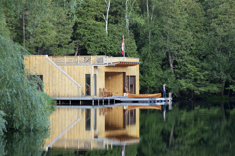Wooden Boathouse with canoe on dock surrounded by trees reflected in water
