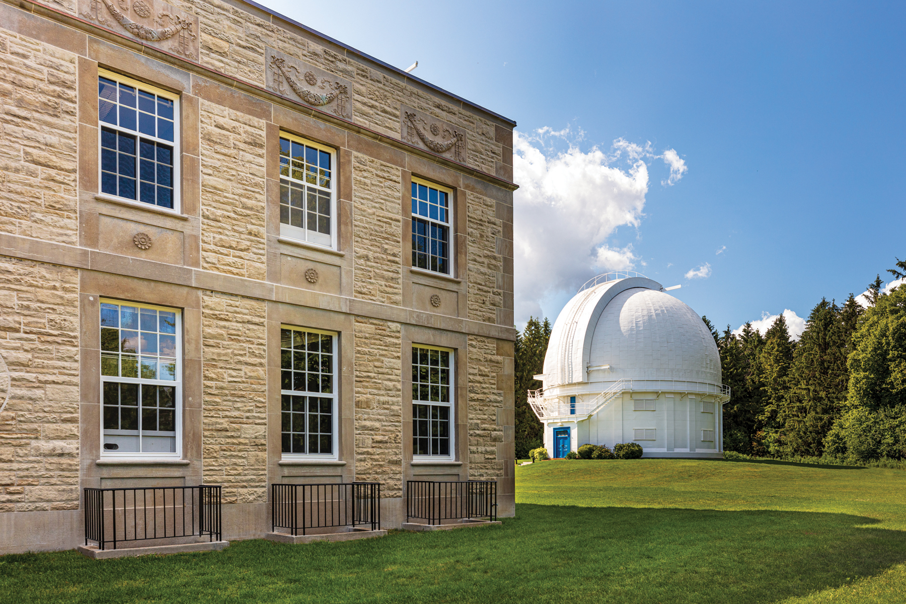 View of white observatory with blue door from behind two-storey Administration Building