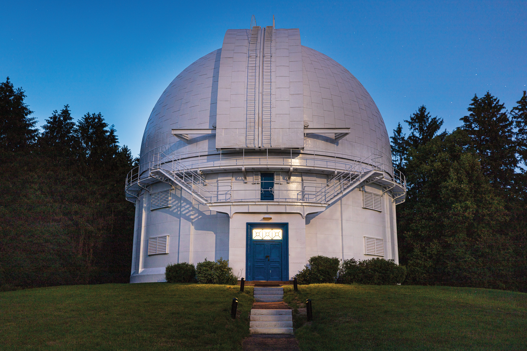 White Observatory with illuminated blue door with green lawn and trees at dusk